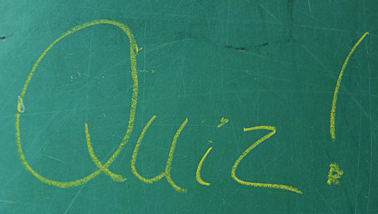 Grammar quiz signified by 'Quiz' written on a green blackboard.